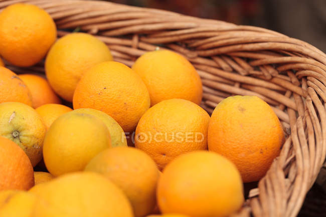 Fresh oranges in fruit basket — Stock Photo
