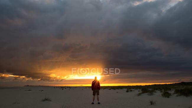 Homme debout sur la plage au coucher du soleil — Photo de stock
