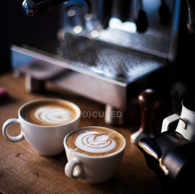 Close-up view of two cups with cappuccino in front of coffeemaker — Stock Photo