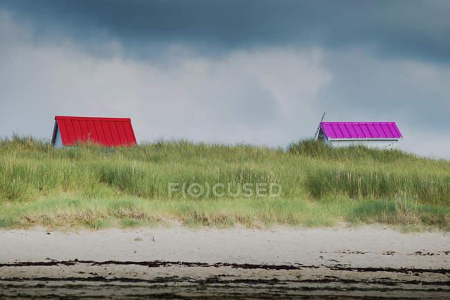 Telhados coloridos de cabanas na grama verde, na beira-mar — Fotografia de Stock