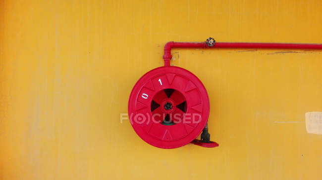 Coiled fire hose on red painted reel — Stock Photo