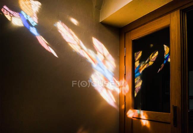 Interior view light beam of colored glass window on wall near door — Stock Photo