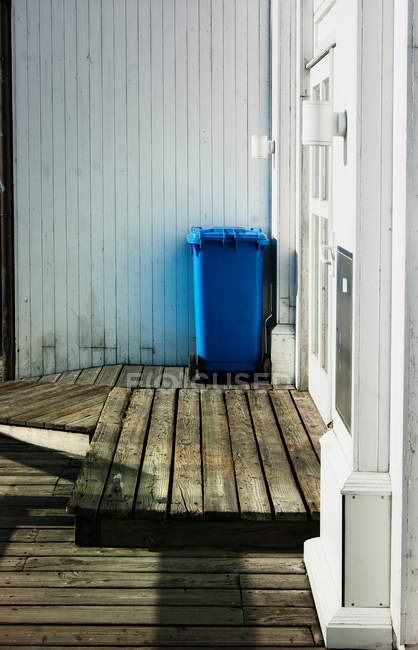 Blue trash can on wooden flooring — Stock Photo