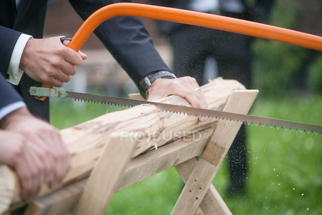 Cropped view of men in suits working with saw — Stock Photo