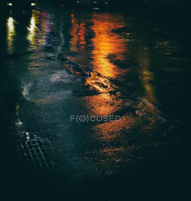 Route d'asphalte mouillé avec des reflets de feux orange, temps pluvieux — Photo de stock