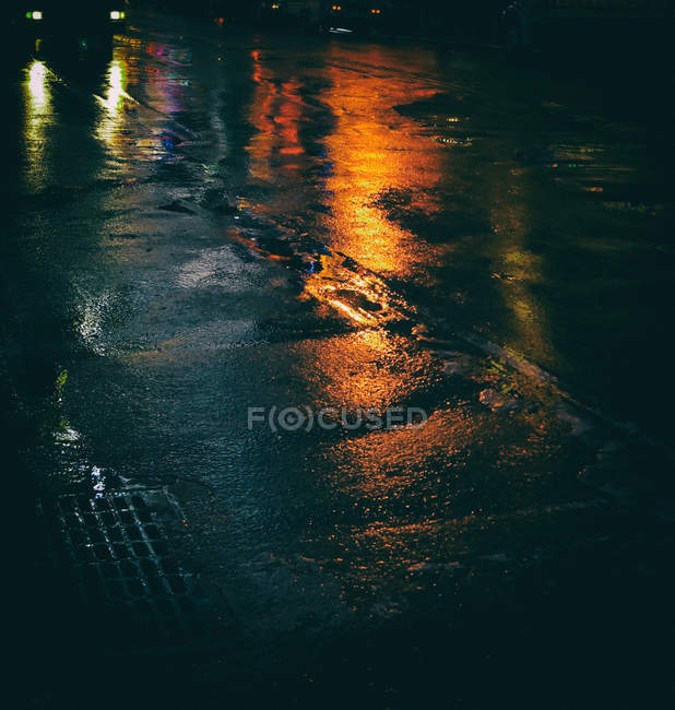 Wet asphalt road with orange lights reflections, rainy weather — Stock Photo