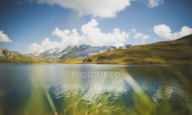 Горное озеро, в окружении гор и холмов — стоковое фото