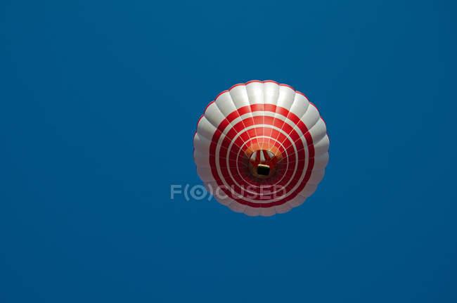 Globo de aire caliente en el cielo azul - foto de stock