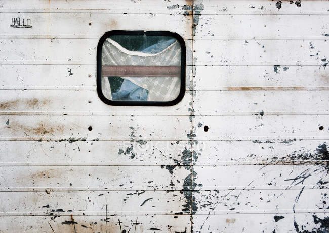 Vista de primer plano de pared shabby remolque con ventana - foto de stock