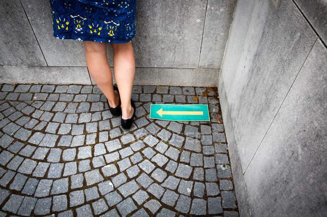 Rear view of female legs standing on floor beside arrow left sign — Stock Photo