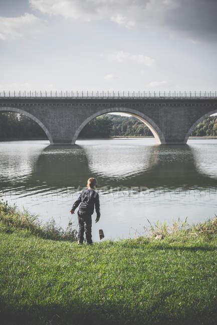 Garçon, debout devant l'énorme pont gris — Photo de stock