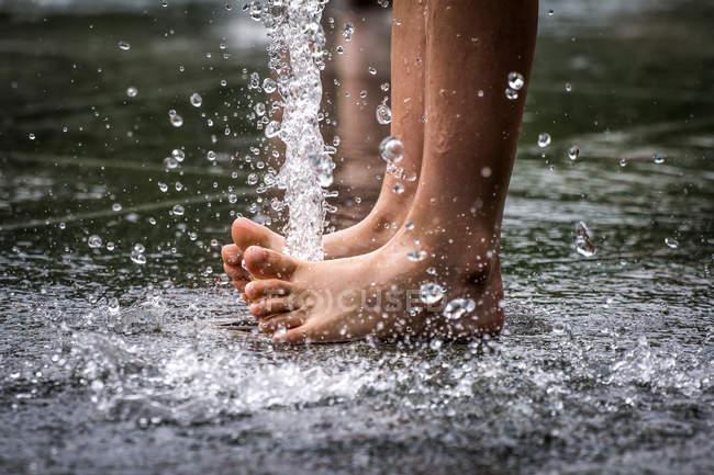 Ritagliate la vista dei piedi di persona in acqua della Fontana — Foto stock