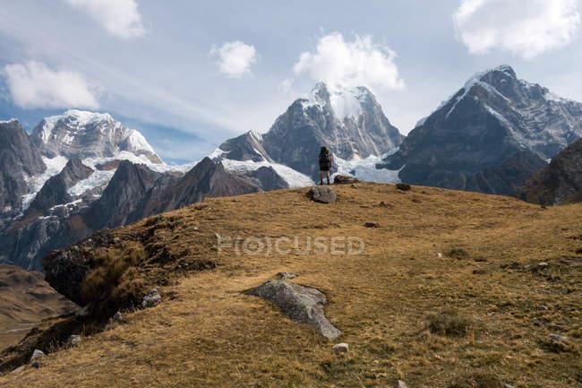 Persona di viaggiatore guardando picco di montagne e cielo nuvoloso — Foto stock