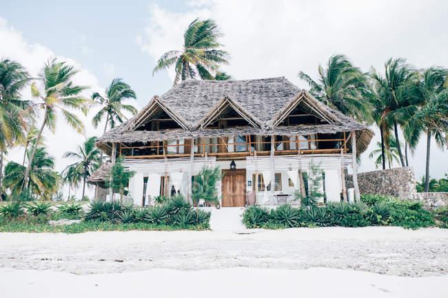 Crescente verde palmeiras na praia tropical com casa — Fotografia de Stock