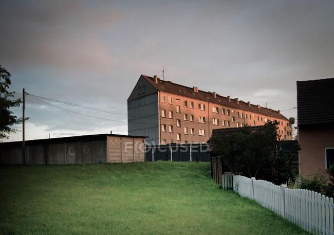 Scena urbana con edifici e prato verde nella luce del tramonto — Foto stock