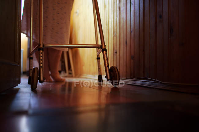 Senior woman using walker at home — Stock Photo