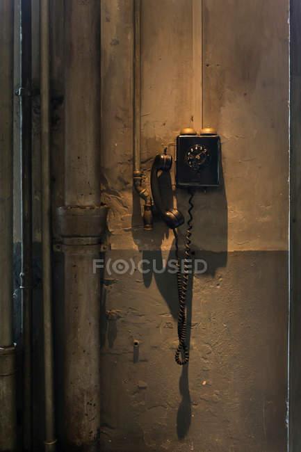 Vintage Telefon in der Nähe von Rohren auf schäbige Betonwand — Stockfoto