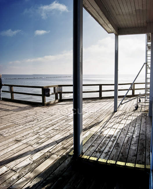 Scenic view with far off outdoor place by the sea and wooden footbridge — Stock Photo