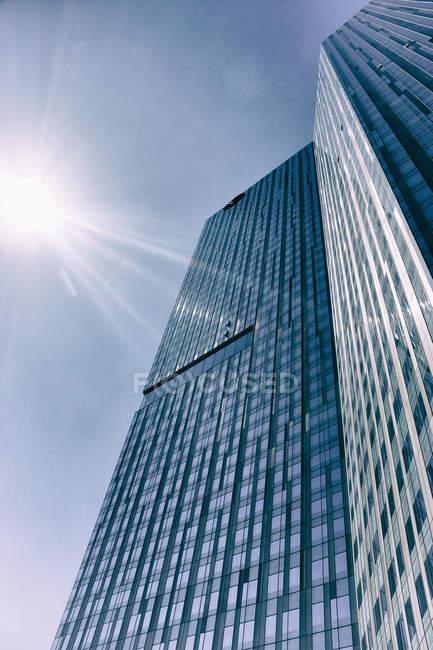 Vista inferior do arranha-céu moderno, com fachada de vidro na luz solar — Fotografia de Stock