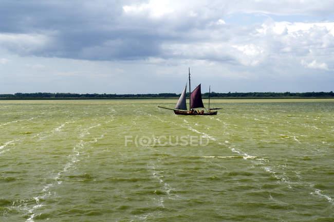 Paysage avec vue la côte et le voilier sur l'eau verte — Photo de stock