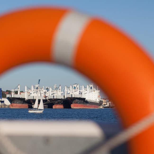 Port avec les cargos et bateaux à voiles, voir au travers de la bouée de sauvetage — Photo de stock
