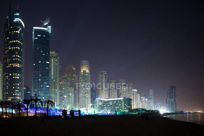 Paisagem urbana da metrópole de Dubai, com arquitetura moderna, iluminada à noite, nos Emirados Árabes Unidos — Fotografia de Stock