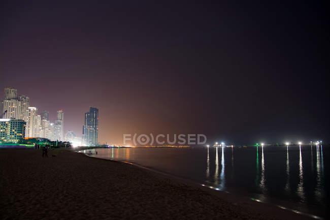 Paisagem urbana da metrópole de Dubai iluminado à noite, nos Emirados Árabes Unidos — Fotografia de Stock