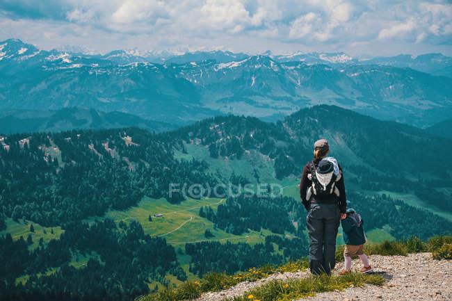 Vista posterior de la mujer de viajero con los niños en las montañas - foto de stock