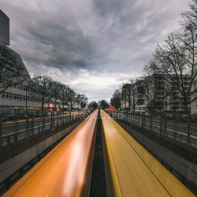 Городской пейзаж и освещенная дорога с трафика движения размытия в угрюмый день — стоковое фото