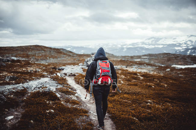Traveler with backpack hiking in mountains — Stock Photo