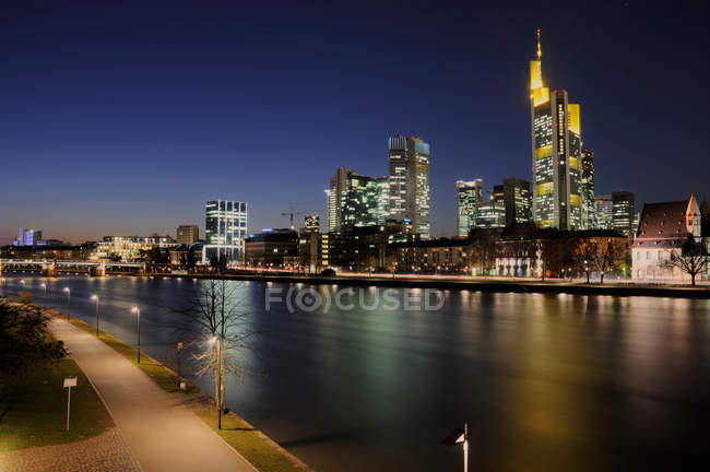 Town with illuminated buildings and river at night — Stock Photo