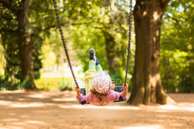 Little child girl on swings in playground — Stock Photo