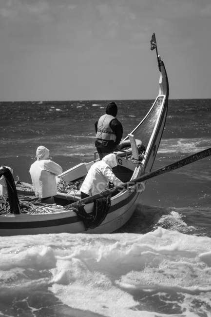 Vista traseira do três homem nadando no barco no mar, monocromático — Fotografia de Stock