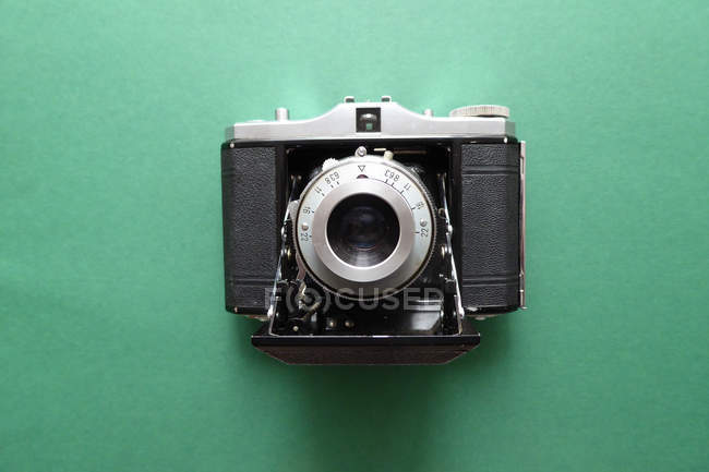 Top view vintage film camera on green surface — Stock Photo