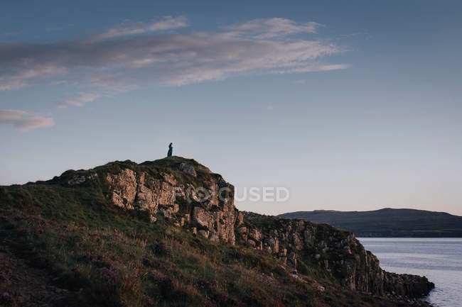 A woman standing on top of a cliff by the rocks under a blue cloudy sky — Stock Photo