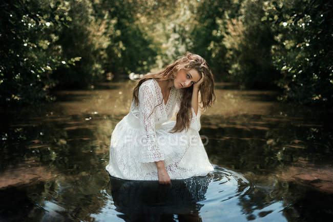 Young woman crouching in the water surrounded by trees in a forest — Stock Photo