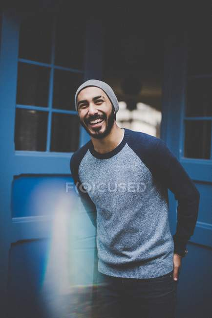 Portrait of smiling man in hat and casual clothing at blue door — Stock Photo