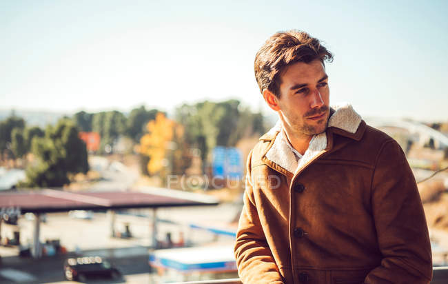 Fashionable man in brown jacket posing outdoors, autumn male fashion — Stock Photo