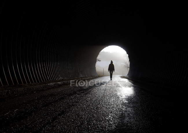 Full length rear view silhouette of a person walking in a tunnel — Stock Photo