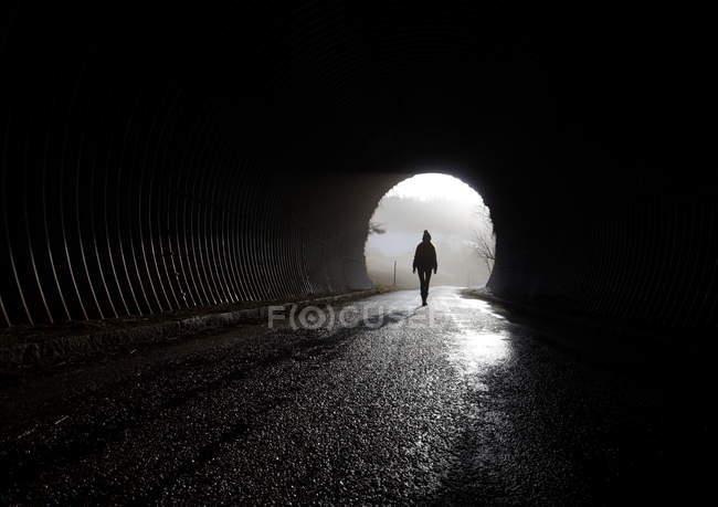 Silhueta de vista traseira do comprimento total de uma pessoa caminhando em um túnel — Fotografia de Stock