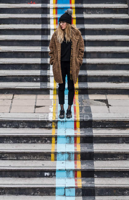 Full length portrait of a woman wearing warm clothing standing on steps — Stock Photo