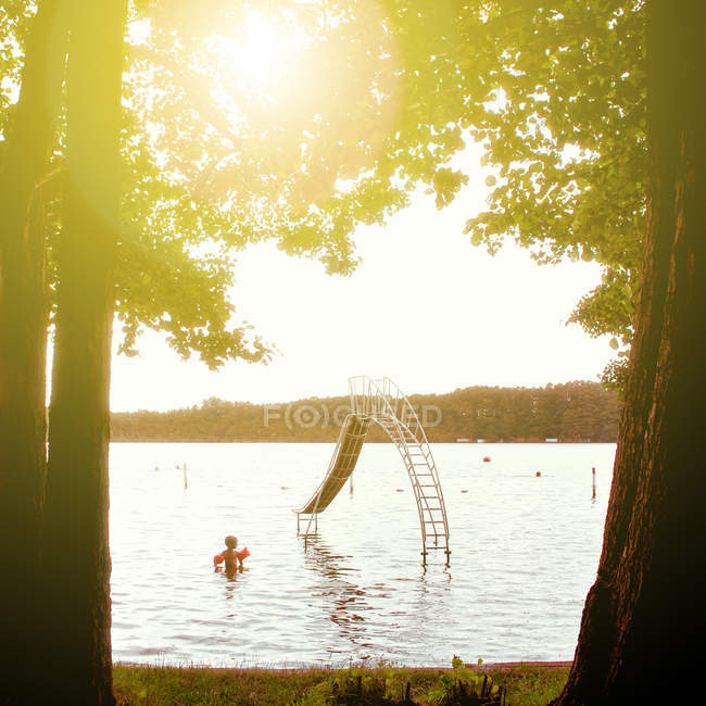 Scenic view of a young boy in the lake  surrounded by trees on a sunny day — Stock Photo