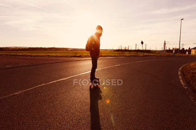 Full length of a man on longboard standing on road. — Stock Photo