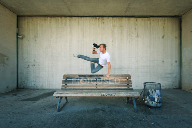 A man jumping over bench in mid air with a film camera — Stock Photo