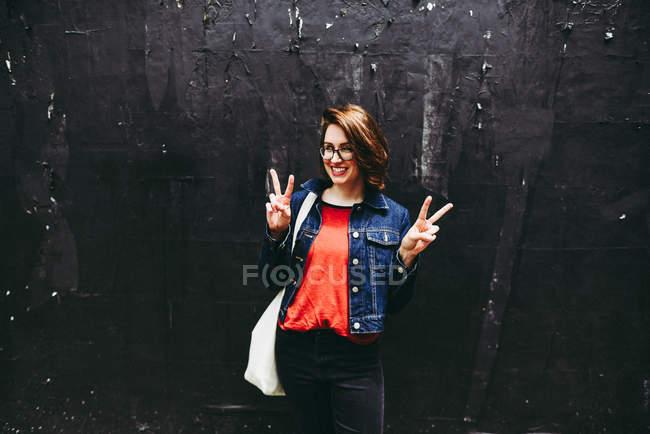 Souriante jeune femme debout à l'extérieur au mur foncé et gesticulant de paix avec les doigts — Photo de stock