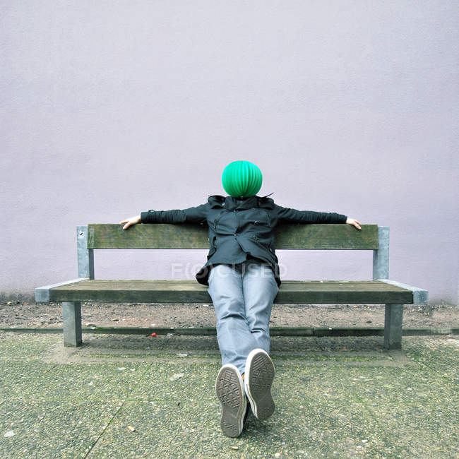A person sitting on a bench with a lantern on his head — Stock Photo
