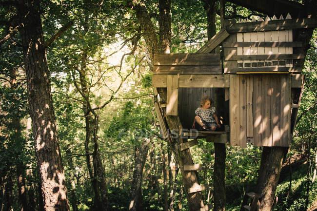 Хлопчик сидить в дереві будинку в зеленому лісі — стокове фото