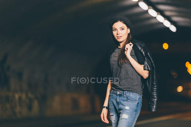 Fashionable woman in casual clothing standing in tunnel — Stock Photo
