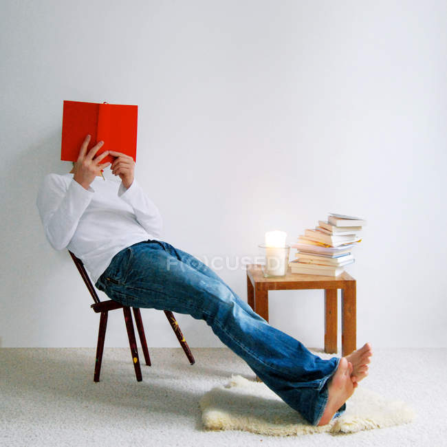 Man sitting on a chair reading a book indoors — Stock Photo