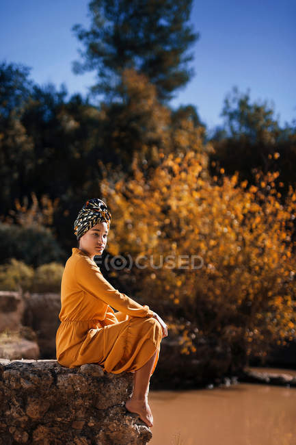 Full length shot of young African woman sitting in nature and wearing long yellow dress — Stock Photo